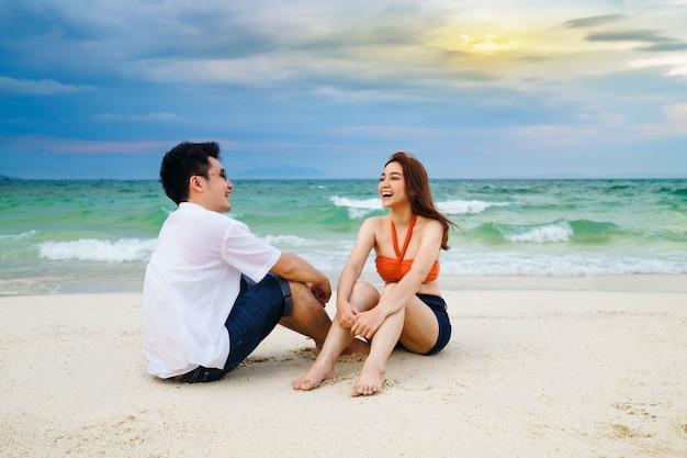 Jovem casal feliz sentado na praia do mar na ilha de koh munnork, rayong, tailândia
