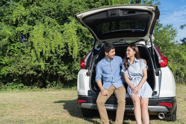 Jovem casal feliz sentado nas costas de um carro aberto