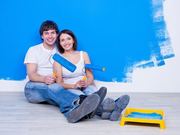Jovem casal feliz sentado no chão perto da parede pintada