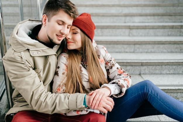 Jovem casal feliz sorrindo com os olhos fechados e sentado na escada.