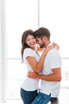 Jovem casal feliz sorrindo e se abraçando em casa