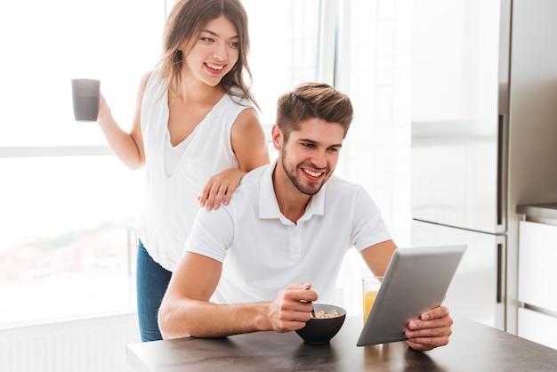 Jovem casal feliz tomando café da manhã e usando tablet na cozinha
