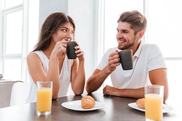 Jovem casal feliz tomando café da manhã na cozinha juntos