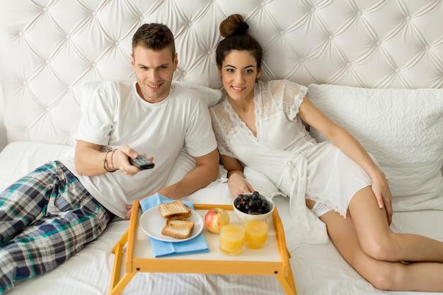 Jovem casal feliz tomando café da manhã no quarto de luxo