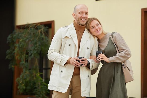 Jovem casal feliz tomando café e curtindo seu passeio pela cidade