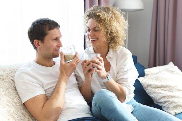 Jovem casal feliz tomando café em casa