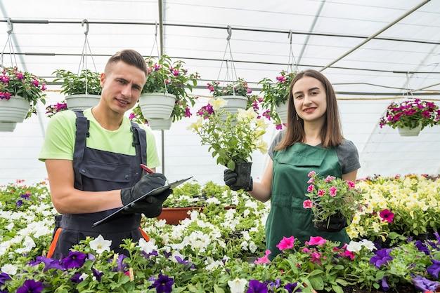 Jovem casal feliz trabalhando com flores em estufa industrial. estilo de vida