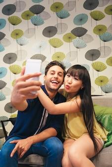 Jovem casal feliz usando smartphone no bar. eles estão no caixão