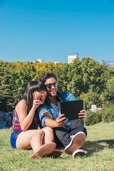 Jovem casal feliz usando tablet sentado no parque
