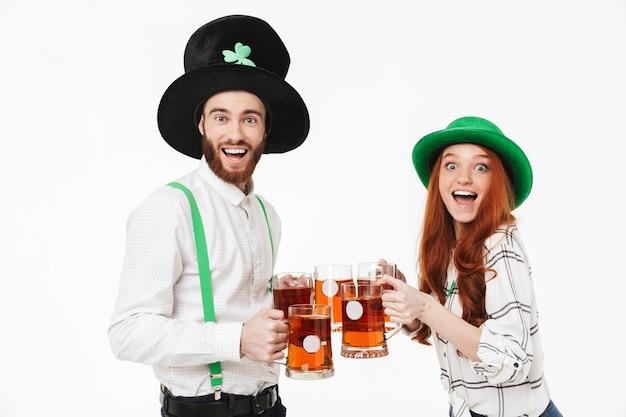 Jovem casal feliz vestindo fantasias, comemorando o dia de st patrick isolado em uma parede branca, bebendo cerveja