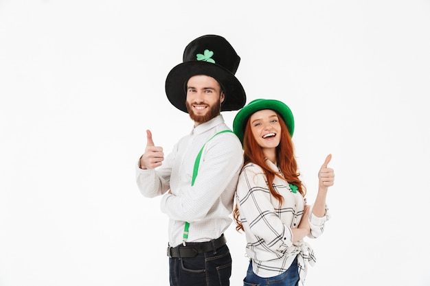 Jovem casal feliz vestindo fantasias, comemorando o dia de st patrick isolado na parede branca, se divertindo juntos, polegares para cima
