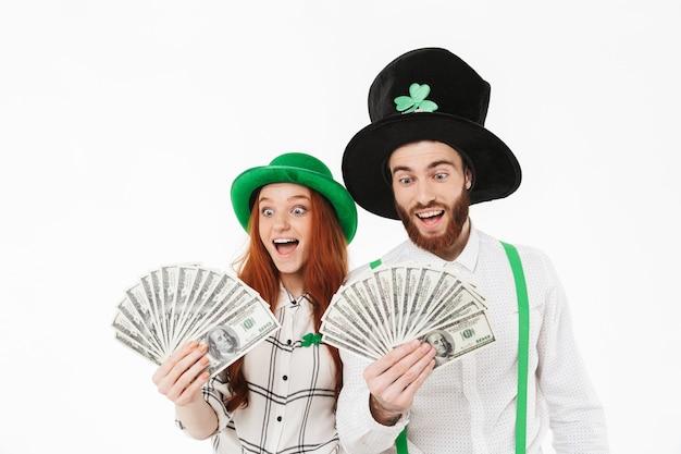 Jovem casal feliz vestindo fantasias, comemorando o dia de st patrick isolado na parede branca, segurando notas de dinheiro