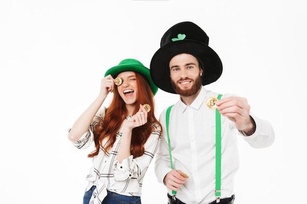 Jovem casal feliz vestindo fantasias, comemorando o dia de st patrick isolado sobre uma parede branca, segurando bitcoins dourados