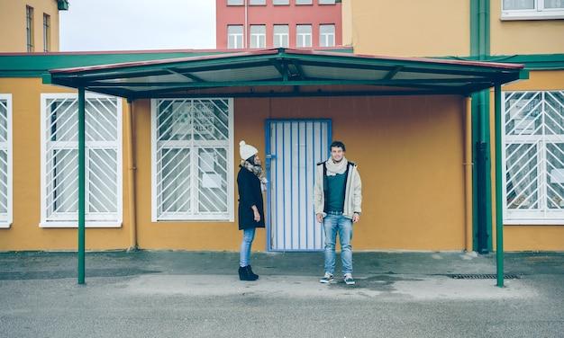 Jovem casal feliz vestindo roupas de inverno, sob um teto metálico ao ar livre em um dia frio e chuvoso
