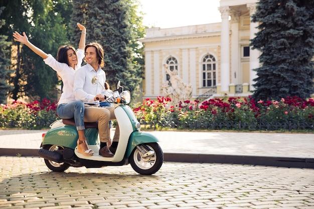 Jovem casal feliz viajando de scooter