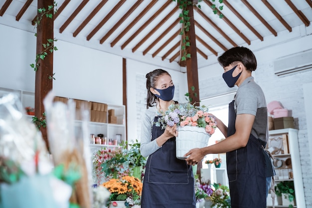 Jovem casal florista usando avental e máscara, segurando uma flor de balde e ajudando um ao outro