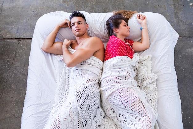 Jovem casal frustrado com sérios problemas deitado na cama