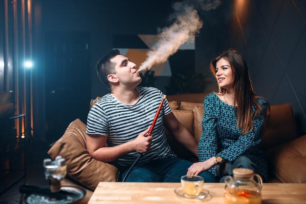 Jovem casal fumando narguilé no sofá de couro do bar, fumando tabaco e relaxando