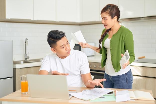 Jovem casal furioso discutindo por causa de suas muitas dívidas em casa