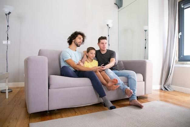 Jovem casal gay bonito e seu filho assistindo programa de tv em casa, sentado no sofá da sala, se abraçando, usando o controle remoto, olhando para longe. conceito de entretenimento familiar e doméstico