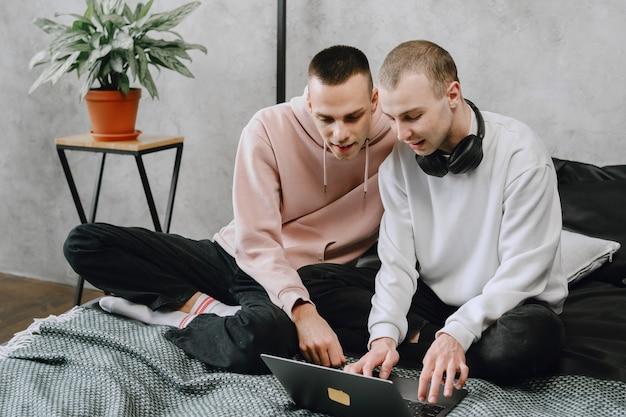 Jovem casal gay sentado na cama usando laptop, usando fones de ouvido, ouvir música juntos, se abraçando ou abraçando.