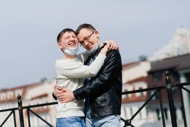 Jovem casal gay usando máscara médica, abraçando a cidade.
