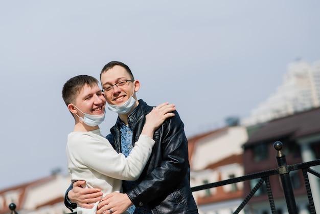 Jovem casal gay usando máscara médica, se abraçando e beijando na cidade.