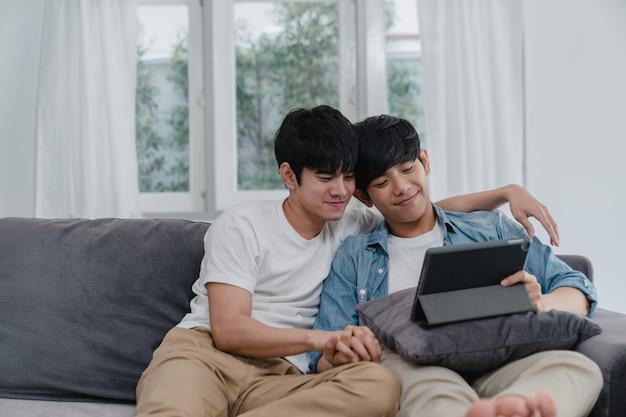 Jovem casal gay usando o tablet em casa. homens asiáticos lgbtq + felizes relaxam divertidos usando a tecnologia assistindo filme na internet juntos enquanto estão deitados no sofá na sala de estar.