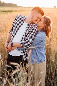 Jovem casal grávida abraça em campos numa bela noite de verão. gratidão e felicidade. gravidez e cuidados. felicidade e ternura. cuidado e atenção. amor e atenção.