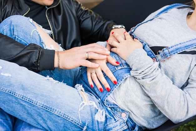 Jovem casal grávida de mãos dadas na grande barriga.