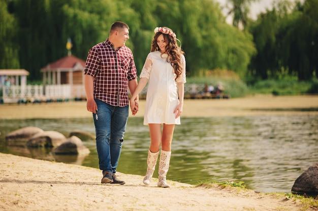 Jovem casal grávida romântica feliz está andando na natureza perto do lago no parque de verão. mulher grávida esperando um bebê. futura mãe e pai, família. dia dos pais