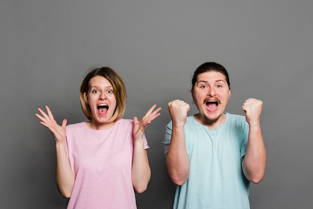 Jovem casal gritando de alegria contra o fundo cinza