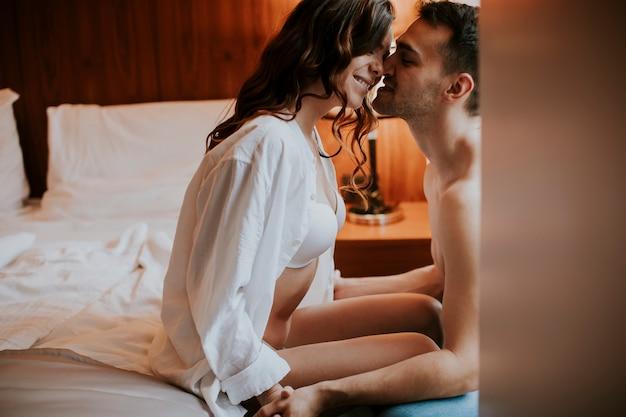 Jovem casal heterossexual adulto deitado na cama no quarto