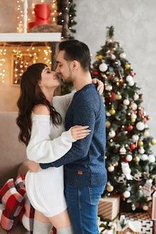 Jovem casal heterossexual doce posando no interior da sala decorada para o feriado de ano novo