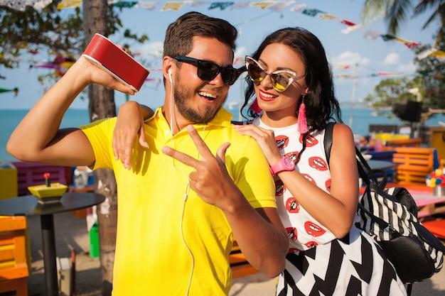 Jovem casal hippie elegante nas férias de verão na tailândia, glamour, roupas de tendências da moda, óculos de sol, romance tropical, sorrindo, feliz, ouvindo música, clima de festa, café na praia