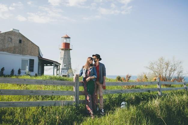 Jovem casal hippie estilo indie apaixonado caminhando pelo campo, de mãos dadas, farol no fundo, dia quente de verão, ensolarado, roupa boêmia, chapéu