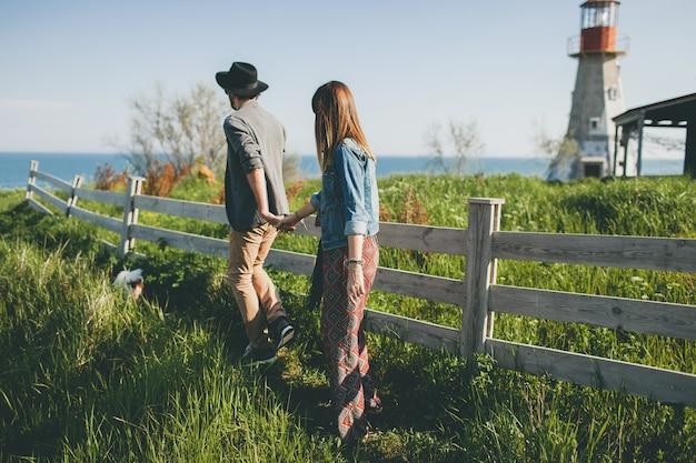 Jovem casal hippie estilo indie apaixonado caminhando pelo campo, de mãos dadas