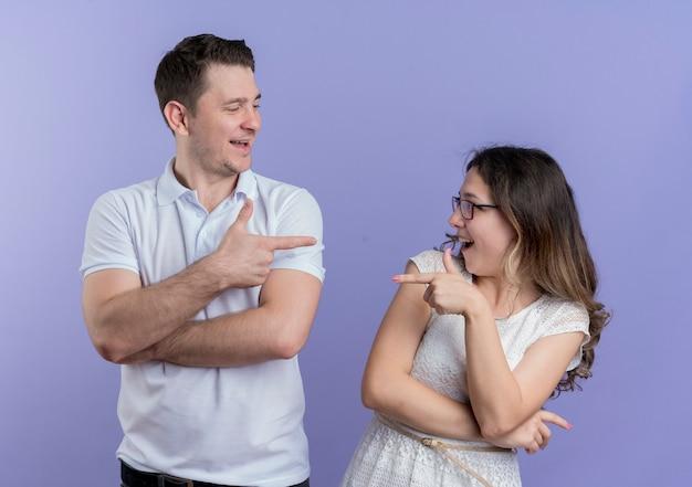 Jovem casal, homem e mulher, apontando um para o outro com os dedos indicadores sorrindo em pé sobre a parede azul