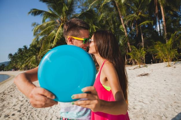 Jovem casal homem e mulher brincando de disco voador na praia tropical, férias de verão, amor, romance, humor feliz, sorrindo, se divertindo, roupa hipster, óculos de sol, shorts jeans, ensolarado, humor positivo