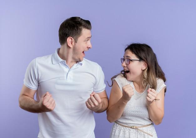 Jovem casal, homem e mulher, cerrando os punhos felizes e animados em pé sobre a parede azul