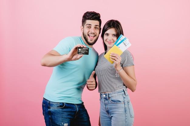 Jovem casal homem e mulher com bilhetes de avião e cartão de crédito