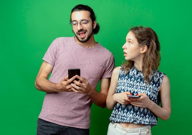 Jovem casal homem e mulher com smartphones mulher surpresa e confusa olhando para o namorado por cima da parede verde
