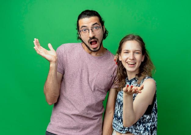 Jovem casal, homem e mulher, confusos com os braços abertos enquanto perguntam em pé sobre uma parede verde