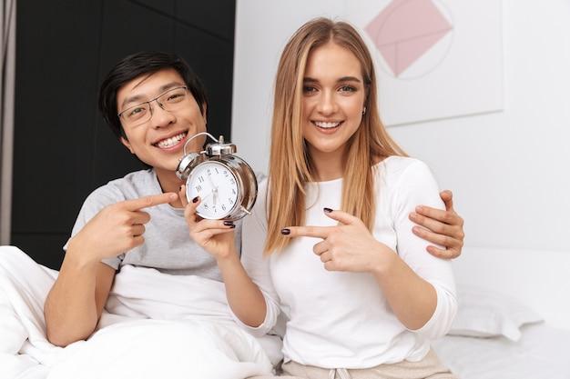 Jovem casal, homem e mulher, deitados juntos na cama em casa, segurando o despertador