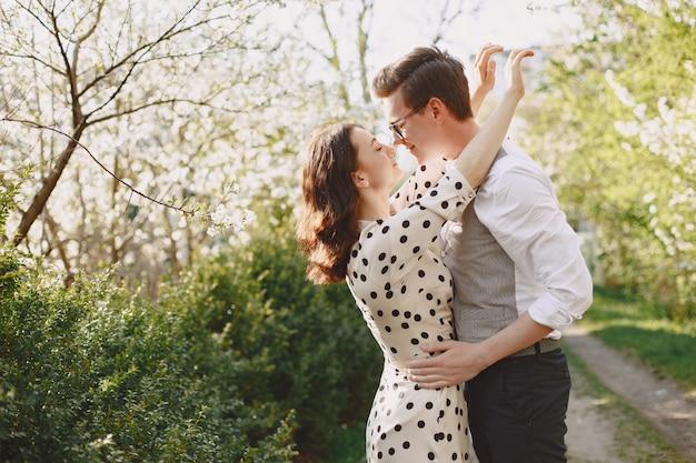 Jovem casal homem e mulher em um jardim florescendo