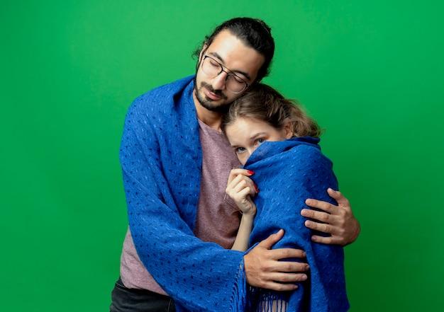 Jovem casal, homem e mulher, feliz homem abraçando sua amada namorada, envolvendo-a em um cobertor quente em pé sobre um fundo verde