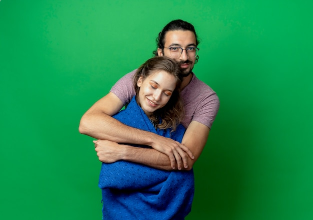Jovem casal, homem e mulher, felizes apaixonados, lindo homem abraçando sua amada namorada com um cobertor em pé sobre um fundo verde