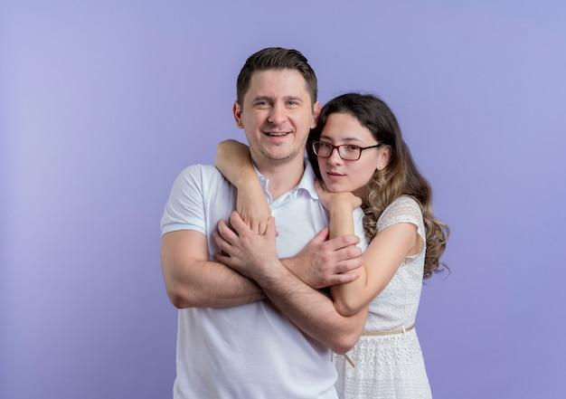 Jovem casal, homem e mulher, felizes e apaixonados se abraçando, olhando para a câmera, sorrindo em pé sobre a parede azul
