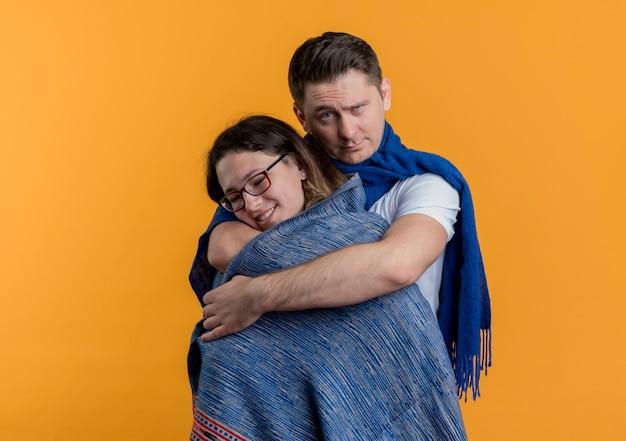 Jovem casal homem e mulher felizes no amor, homem cobrindo a namorada com um cobertor quente com cara séria em pé sobre a parede laranja