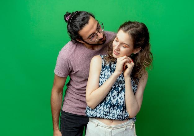 Jovem casal homem e mulher felizes no amor, homem vai beijar sua namorada tímida por cima de uma parede verde